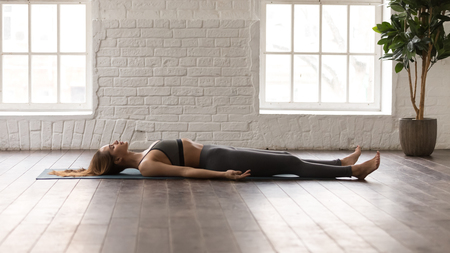 Calm woman in grey sportswear, pants and bra practicing yoga, lying in Savasana, Dead Body pose on mat, beautiful girl resting after working out at home or in yoga center with white walls 스톡 콘텐츠 - 118059210