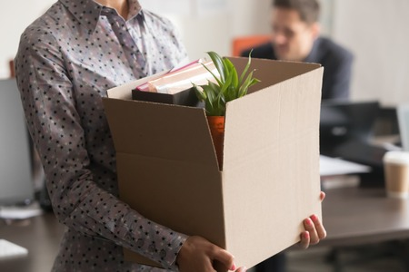 Close up view of new female employee intern holding cardboard box with belongings start finish job in company office, busnesswoman newcomer worker get hired fired on first last day at work concept Foto de archivo