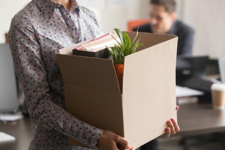 Vista de cerca de la nueva empleada pasante que sostiene una caja de cartón con sus pertenencias, comienza a terminar el trabajo en la oficina de la empresa, la trabajadora recién llegada es contratada despedida el primer último día en el concepto de trabajo