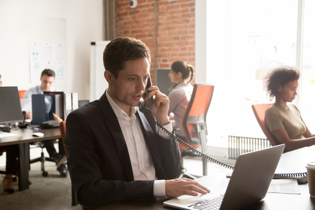 Serious businessman in suit making call negotiating consulting customer looking at laptop in modern office space, salesman broker marketer talking on phone for telephone job interview at workplace