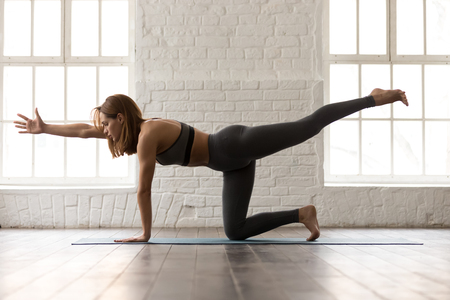 Attractive woman in grey sportswear, bra and leggings practicing yoga, standing in Bird dog pose, beautiful girl doing Donkey Kick exercise at home or in yoga studio with white walls background 写真素材