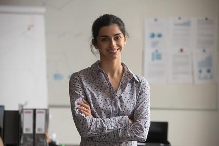 Giovane donna d'affari indiana professionale che guarda la telecamera in ufficio, allenatore donna d'affari fiduciosa, responsabile marketing aziendale femminile, felice dipendente indù millenario sorridente in posa per il ritratto