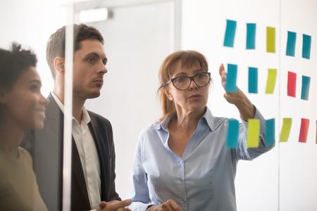 Femme d'affaires d'âge moyen mentor coach leader expliquant la stratégie du projet montrant post-it des notes autocollantes sur le mur de verre, plan de travail de remue-méninges de l'équipe d'affaires sérieuse au siège social de l'entreprise