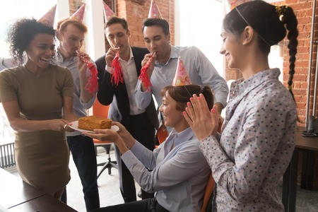 Multicultural employees in party hats congratulate female colleague celebrate happy birthday presenting cake blow whistles, diverse corporate workers having fun make surprise greeting boss in office