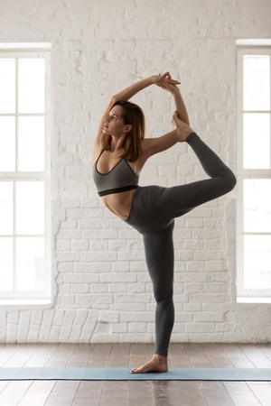 Attractive young woman doing Natarajasana exercise, Lord of the Dance pose, sporty girl in grey sportswear, leggings and bra practicing yoga, working out at home or in yoga studio, vertical photo