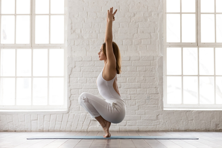 Concentrated sporty woman in white sportswear, pants and top standing in Utkatasana pose, Squat, Chair exercise, attractive girl training in modern yoga studio or at home
