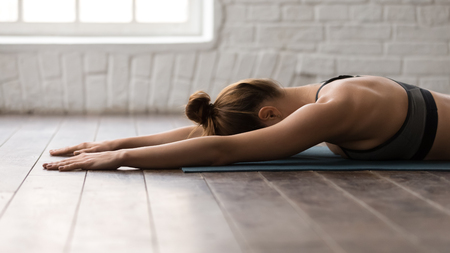 Young woman practicing yoga, lying face down on mat, relaxing after training, beautiful girl in grey sportswear, bra working out at home or in yoga studio with wooden floor Stock Photo