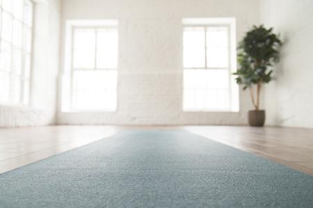 Abgerollte Yogamatte auf Holzboden in leerem Raum, modernes Yogastudio oder Fitnesscenter mit großen Fenstern und weißen Ziegelwänden, Sportgeräten zum Meditieren oder Übungen hautnah