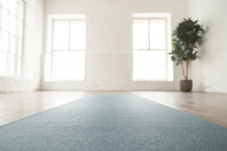Close up unrolled yoga mat on wooden floor in empty room, modern yoga studio or fitness center with big windows and white brick walls, sport equipment for meditating or exercises