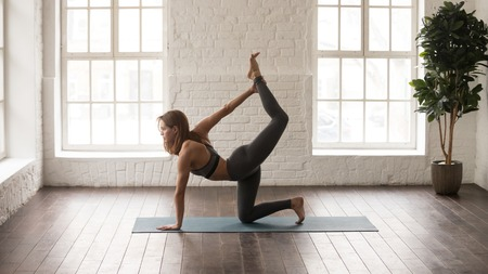 Attractive woman in grey sportswear, bra and leggings practicing yoga, standing in tiger pose, beautiful girl doing Bird dog exercise at home or in yoga studio with white walls background Stock Photo