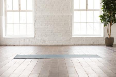 Yogamatte auf Naturholzboden in leerem Raum im Fitnesscenter, bequemer Platz für Sportübungen, große Fenster und weiße Ziegelwände, moderner Yoga-Klassenraum mit niemandem
