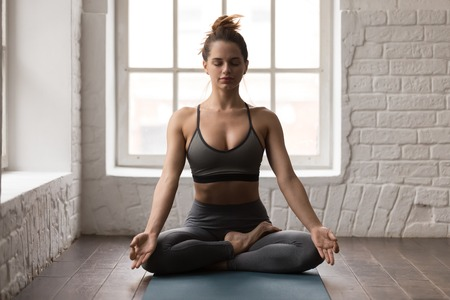 Calm woman with closed eyes practicing yoga, sitting in Padmasana pose on mat, Lotus exercise, attractive sporty girl in grey sportswear, leggings and bra working out at home or in yoga studio Standard-Bild