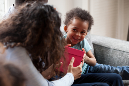 Funny little mixed race toddler boy give birthday present to mom sitting together with parents on couch, cute small African American kid laugh making gift box surprise to young mother Reklamní fotografie