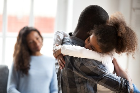 Cute little preschool African American daughter hug young father showing love and care, smiling small child girl embrace black father happy to spend time with parents at home. Family wellbeing concept