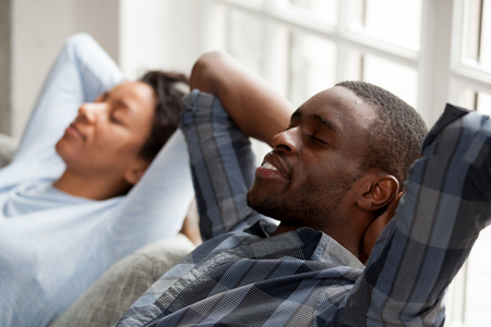 Close up of calm mixed race man and woman lying on couch hands over head relaxing together, peaceful happy black couple rest on sofa with eyes closed, dreaming or meditating at home