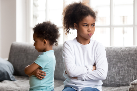 Stubborn small African American brother and sister sit on couch back to back avoid talking, offended mixed race siblings boy and girl with arms crossed angry after fight not speaking to each other Stock Photo
