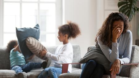 Mamá negra joven deprimida se siente molesta sufriendo dolor de cabeza cansada de niños pequeños ruidosos que juegan, madre afroamericana soltera molesta privada de dormir o relajarse, agotada de niños desobedientes
