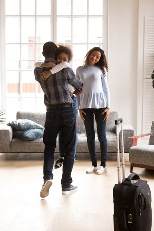 Excited little African American daughter hug young father meeting him come home from business trip, happy black mother and kid smiling glad to reunite with dad, embracing him. Family reunion concept Imagens