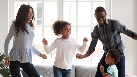 Happy young mixed race family of four have fun together in living room, African American mom and dad entertain with little kids, dancing at home, black parents enjoy spending time with small children Stock Photo