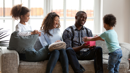 Funny little African American boy toddler make surprise present for excited young dad, cute small mixed race kid give birthday box to smiling father sitting together with black family on couch at home Stock Photo