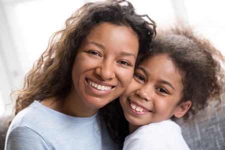 Headshot portrait of happy young black mom and cute preschool daughter hug cheek to cheek looking at camera, smiling mixed race mother and preschool child embrace shared close moment together