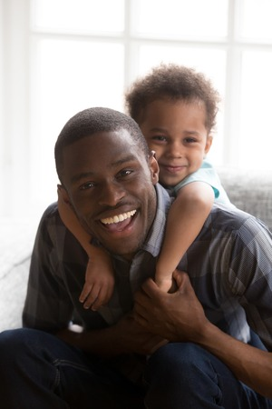 Small funny kid piggyback smiling African American young dad relaxing together on home couch, happy millennial black father have fun with little child, making family portrait posing for picture