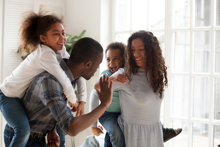 Excited little mixed race kids piggyback young black parents having fun together at home, happy small brother and sister play with mom and dad relaxing in living room, ride them laughing and giggling