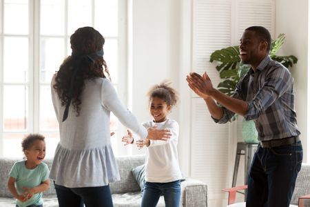 Happy African American young family have fun together playing hide and seek game in living room, black parents spend time with little kids, laughing engaged in entertaining activity together at home 写真素材