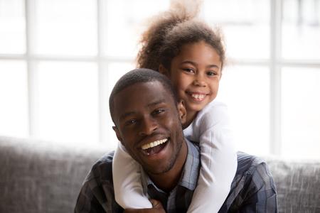 Foto de cabeza de sonriente niña afroamericana a cuestas joven papá feliz relajándose en el sofá juntos, retrato de padre negro emocionado abrazo abrazo con niño pequeño, posando para foto familiar en casa Foto de archivo