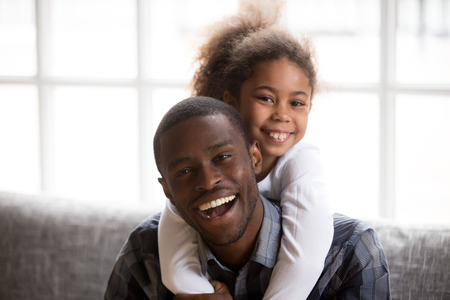 Headshot of smiling little African American girl piggyback young happy dad relaxing on couch together, portrait of excited black father embrace hug with small kid, posing for family picture at home
