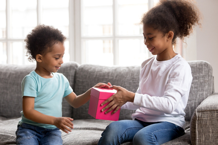 Happy little African American girl sit on couch make surprise present for small toddler brother, caring mixed race sister give gift box to sibling, congratulate with birthday or reconcile after fight Stock Photo