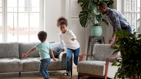 Excited black young dad have fun with mixed race little kids, playing funny game at home, smiling African American father laugh running after and catching small children. Family activity concept Stock Photo