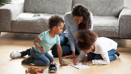 African American young mom spend time with little kids, drawing together with colorful pencils, black mother play with small children painting picture on floor in living room. Family weekend concept