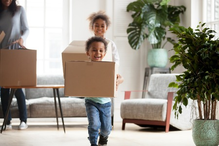 Excited little African American kids run at home holding cardboard boxes happy to move in, smiling small black brother and sister carry carton packages relocating to new house with parents