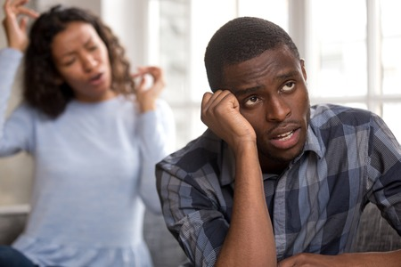 Annoyed African American husband tired of wife lecture or argue, depressed black man bothered of woman blaming him fighting at home, frustrated boyfriend think of breakup. Bad relationship concept Stok Fotoğraf