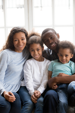 Family portrait of happy young black family sit on couch in living room posing for picture together, smiling African American parents spend time with mixed race relax on sofa at home