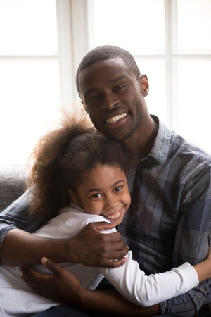 Portrait of young African American dad sit on couch hug teenage girl looking at camera, family picture of black smiling father hold in arms embrace little teen daughter relaxing on sofa at home