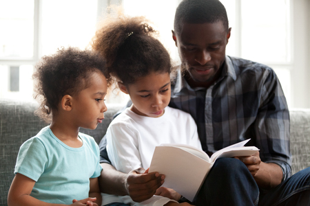 African American young dad spend time together with small kids relaxing on sofa read fairytale or story, black single father sit on couch with little children teaching holding book, rest with family