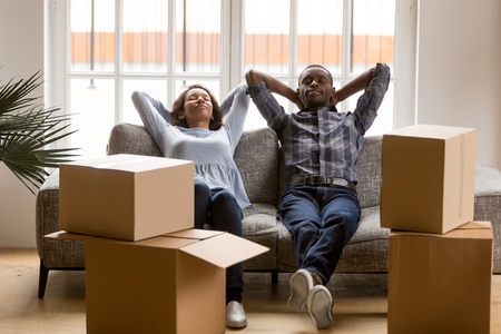 Happy mixed race young husband and wife relax on couch at home tired on moving day, peaceful black couple man and woman lying in living room with cardboard boxed around, exhausted relocating 写真素材