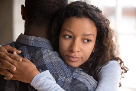 La giovane ragazza di razza mista pensierosa pensa a qualcosa che abbraccia il ragazzo che fa pace dopo il combattimento, preoccupata donna di colore dubbio nelle relazioni, abbracciando con l'amato. Sfiducia di coppia, concetto di barare