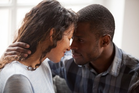 Close up of loving mixed race couple hug relaxing at home together looking in eyes, tender black man and woman embrace having intimate close moment, spend time cuddling enjoy each other company