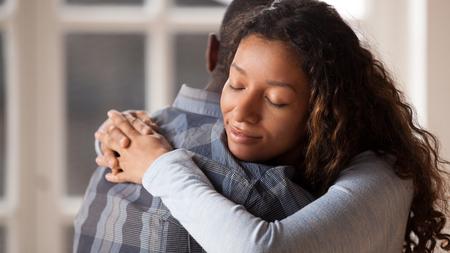 Felice donna di razza mista abbraccio uomo nero marito felice di fare pace dopo il combattimento, amorevole giovane fidanzata riconciliarsi con l'amato fidanzato, abbracciando tenendosi tra le braccia. Concetto di relazioni sane
