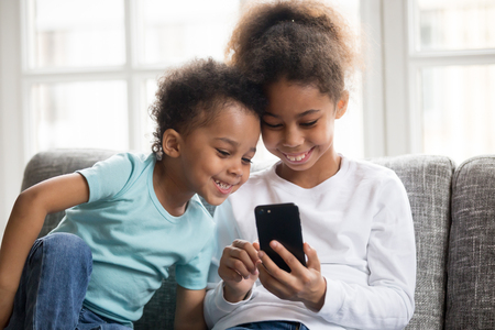 Happy little mixed race kids sit on couch play game on smartphone together, smiling small black brother and sister have fun hold using cellphone, watch funny cartoon. Children and technology concept