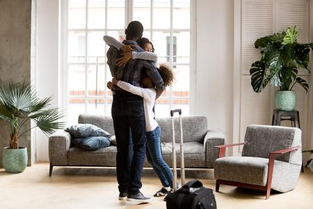 Fröhliche junge afroamerikanische Familie steht im Wohnzimmer umarmt, willkommener schwarzer Vater kommt nach Geschäftsreise mit Koffer nach Hause, gemischtrassige Familie umarmt sich zu Hause, froh, zusammen zu sein. Wiedervereinigungskonzept