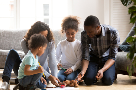 Young African American family spend time at home together drawing with colorful pencils, mixed race parents play with little kids painting picture, playing with toys sitting on floor in living room