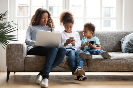 Young African American mom and small kids sit on couch using devices, busy with laptop and smartphones, black modern family addicted to gadgets, little children play on cellphone. Technology concept