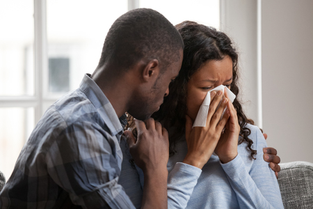 Caring African American husband cheering upset crying wife wiping nose, loving black boyfriend caress support mixed race girlfriend suffering feeling down, supportive man hug spouse showing empathy 版權商用圖片 - 118204235