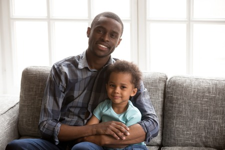 Family picture of happy young African American dad sit on couch hugging little kid, portrait of black millennial father relax with small child embrace on sofa, posing for photo at home together