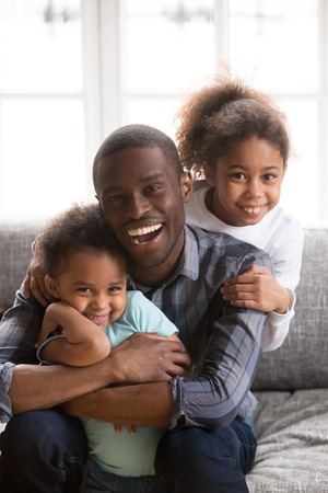 Portrait of happy young African American family of three relax at home sit on couch hugging posing for picture, smiling black dad play with small kids, have fun laughing and embracing on sofa
