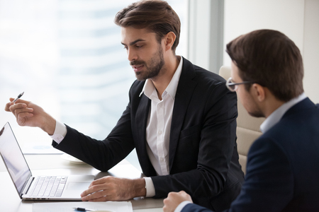 Hombre de negocios serio que explica a un colega que convence al socio o que habla con el cliente que apunta a la computadora portátil, un vendedor de aseguradora del trabajador del banco que habla al cliente de consultoría con una presentación de servicios en línea